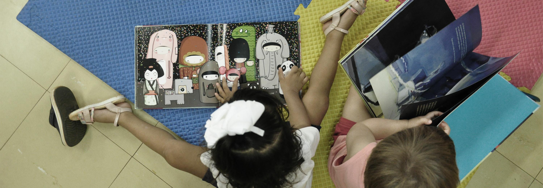 Duas crianças lendo sentadas no chão da biblioteca
