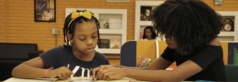 Mulher lendo para criança na biblioteca