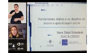 Captura de tela mostra imagem da Professora Sara Dias-Trindade, Intérprete de Libras e slides com apresentação em videochamada.