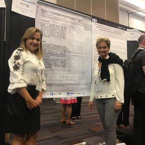 Foto das Professoras Márcia Maria de Souza e Sheila Araújo Teles em frente à Poster contendo resultado de pesquisa.