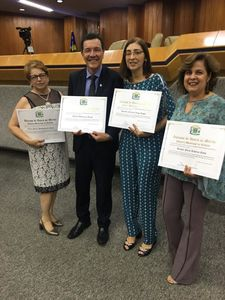 Foto com 4 Docentes homenageados segurando um diploma.