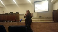 Imagem da Doutora coordenadora do Núcleo de Acessibilidade da UFG Vanessa Santana Dalla Déa falando com o público sobre as questões sobre acessibilidade no ensino superior.